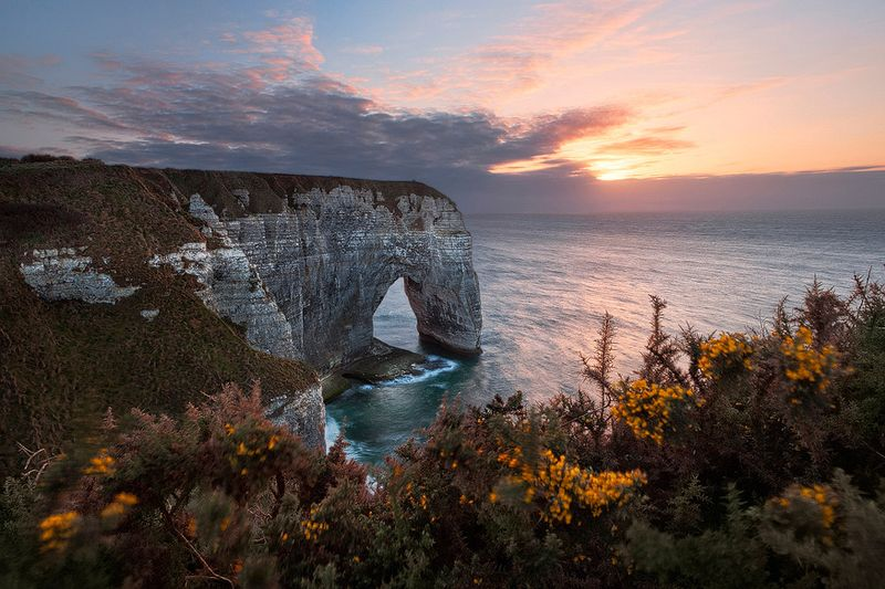 A picturesque sunset above the famous limestone arch Manneporte near Étretat.